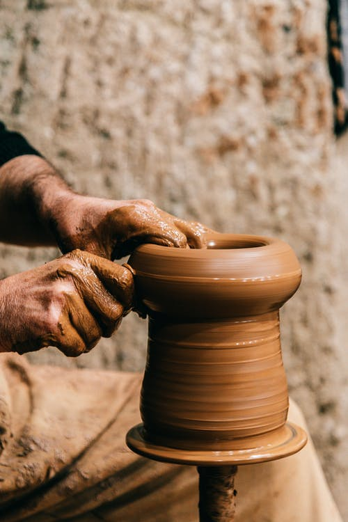 Crop unrecognizable male creating clay vase while working with pottery wheel on blurred background