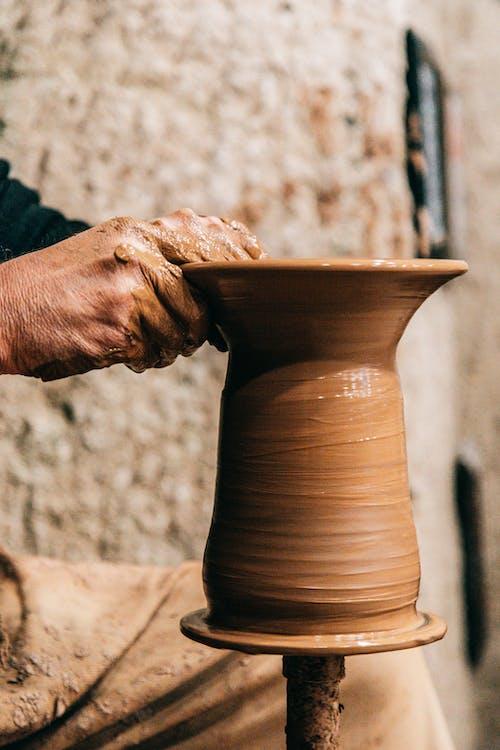 Человек, держащий коричневый глиняный горшок
