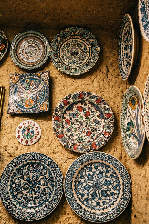 Ceramic decorative handmade plates with various ornaments hanging on stone wall in Morocco
