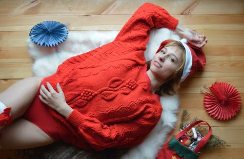 Charming woman in red sweater and Christmas hat lying on wooden floor