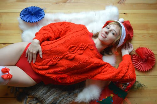 Woman in warm sweater and Christmas hat lying on floor at home