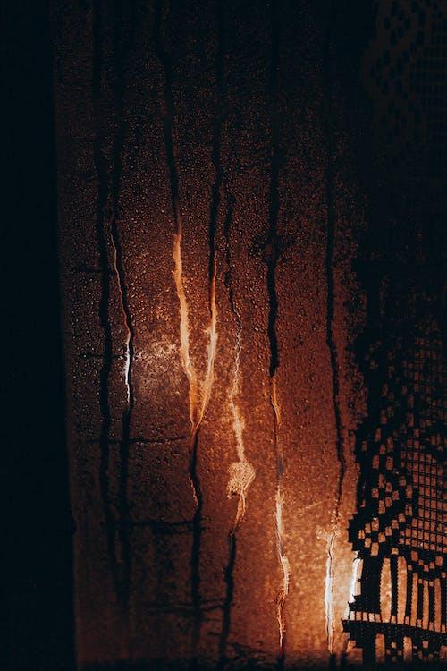 From inside bright orange lights glowing behind steamy window glass at dark night