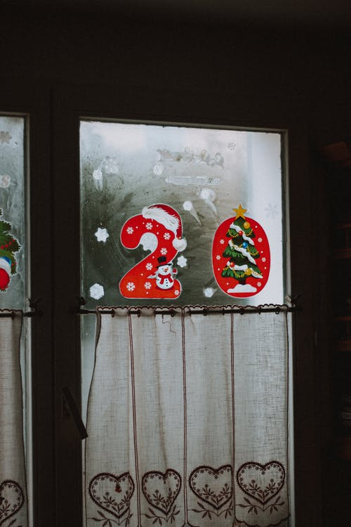 Christmas decoration hanging on misted window with curtains