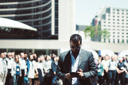 Selective Focus Photography of Man Holding Smartphone While Standing Near People
