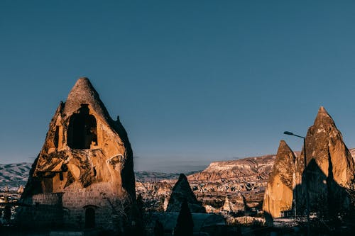 Famous rocky formations with holes and rough surface located in ancient Cappadocia town near hilly terrain against blue sky in Turkey