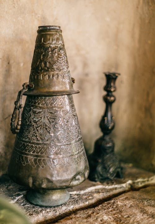 Cone shaped oriental iron incense burner with curving placed near blurred authentic black candlestick near stone wall on rough surface