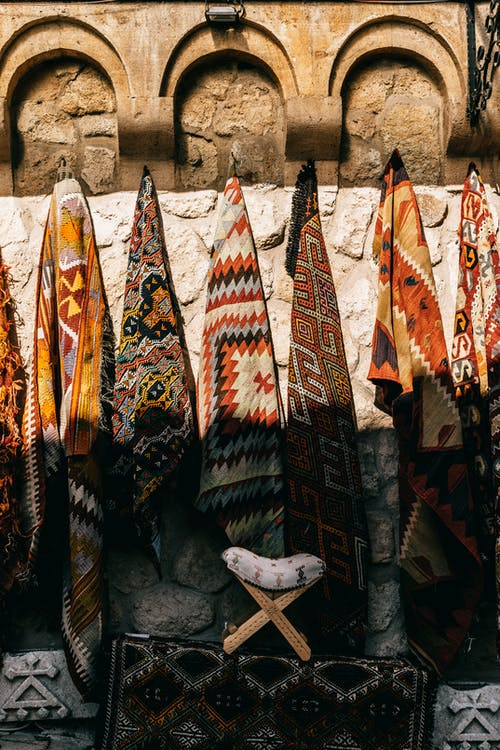 Various colorful traditional carpets with ornamental elements hanging on shabby stone wall on bazaar of ancient town on sunny street