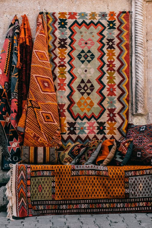 Colorful oriental rugs hanging on wall near sofa with bright cushions with patterns on exhibit in street of old town