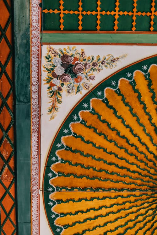 Background of bright oriental patterned element with golden circle floral detail and checkered segments with green frame located on wall