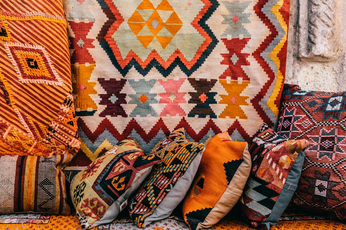 Colorful pillows with patterns placed on couch near abundance of ornamental oriental carpets on bazaar in old city on street