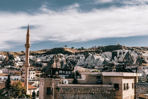 Tall tower located near old houses amidst hilly terrain in ancient town Cappadocia in national park Goreme against cloudy sky