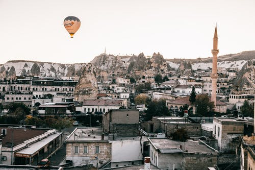 Colorful air balloon flying above shabby buildings and tall tower in famous national park Goreme in Turkey against cloudless sky