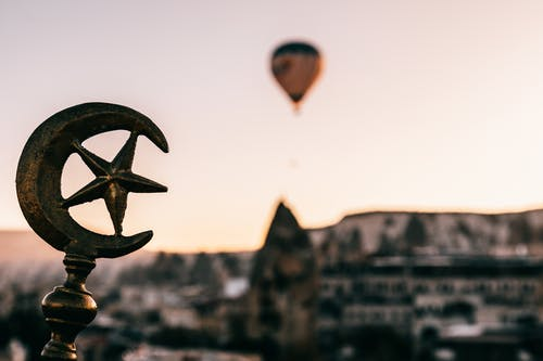 Soft focus of Turkey symbols on top of building against floating air balloon under Cappadocia terrain at dawn