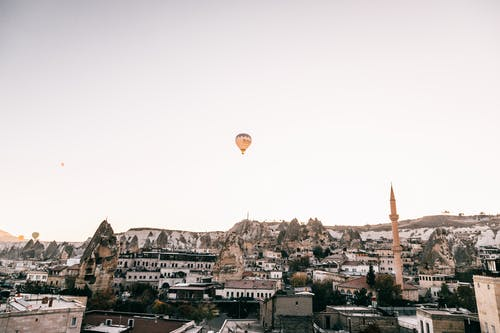 Picturesque scenery of old town with mosque placed among rocky formations in Cappadocia under flying hot air balloon in cloudless sky in daytime
