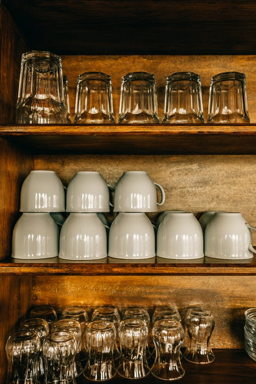 Glasses and cups placed on wooden shelves