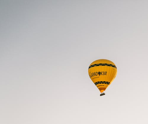 From below of bright yellow hot air balloon flying in cloudless blue sky in Cappadocia in daytime