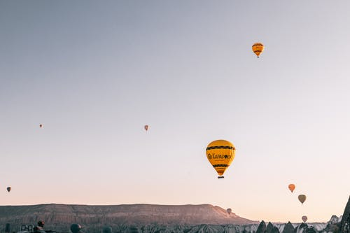 Hot air balloons flying over picturesque highlands at sunrise