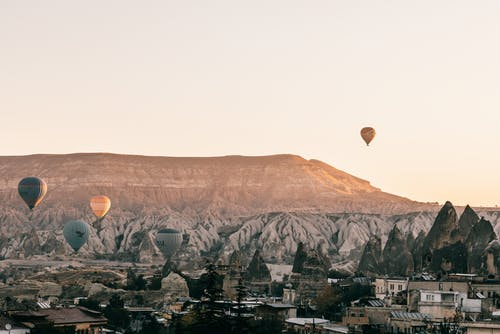 Picturesque scenery of hot air balloons racing over town placed among rocky formations in Cappadocia in Turkey at sunrise
