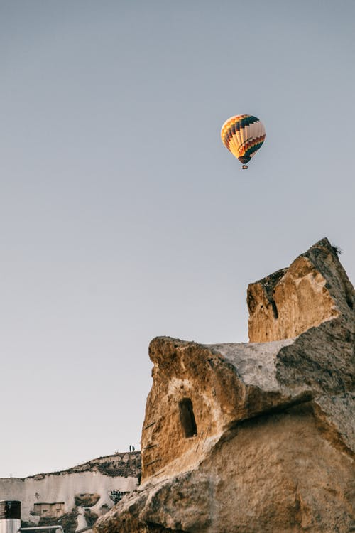Multicolored air balloons flying over rocky formation in daylight