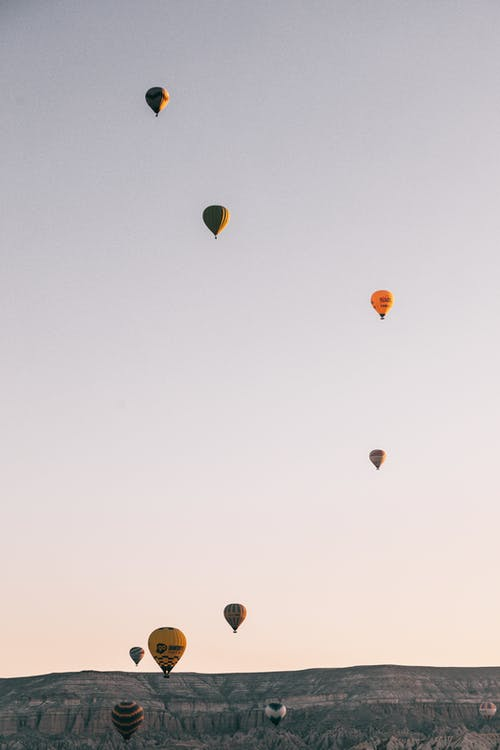 Colorful hot air balloons racing in blue sky over mountainous terrain placed in Cappadocia in daytime