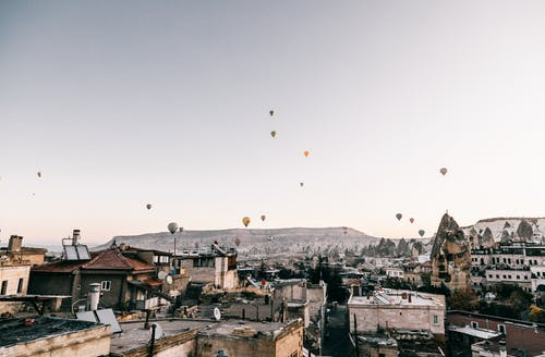 Hot air balloons flying over picturesque town
