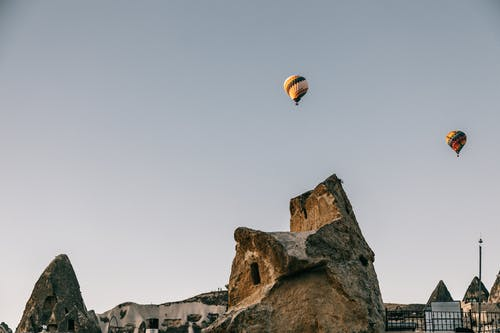 From below of bright hot air balloons flying over rough rocky terrain placed in Cappadocia in Turkey in daytime