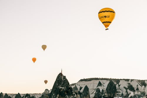 Air balloons flying in sky over rocky highlands