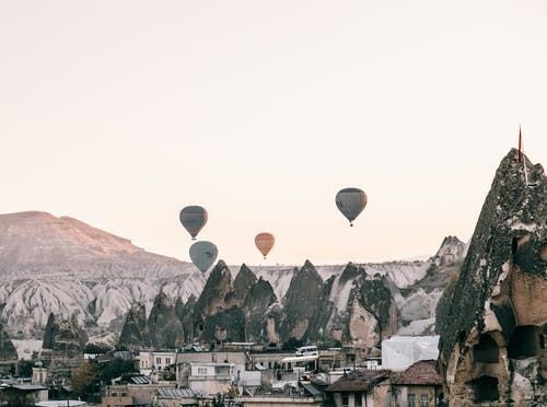 Air balloons flying over town located amidst rocky formations at sundown