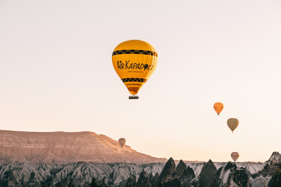 From below of colorful air balloons flying over rocky formations in Goreme National Park located in mountainous valley against cloudless sundown sky