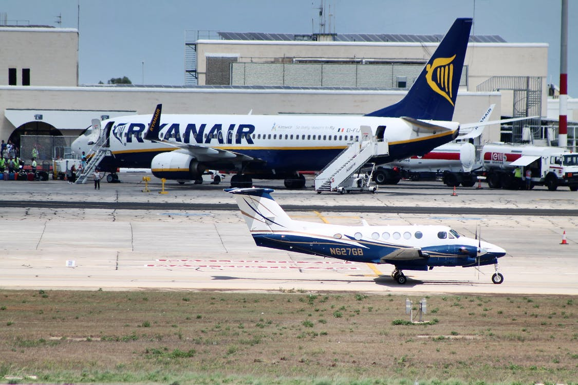 Civil utility and narrow body aircraft parked on runway tracks near modern airport building against cloudless blue sky