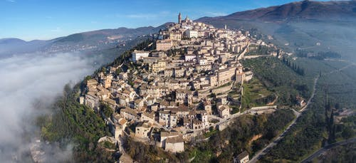 Aerial view of majestic ancient city of San Marino located on green verdant hill on spacious hilly terrain on clear sunny day