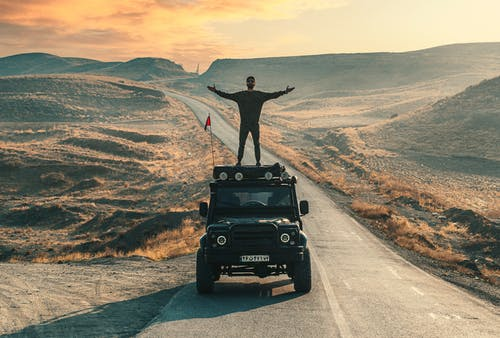Full body of man standing on car roof while travelling through mountainous valley with dry grass in sunny day under bright sky