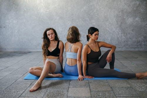 2 Mujeres En Camiseta Negra Sin Mangas Y Leggings Azules Sentadas En Una Estera De Yoga Azul
