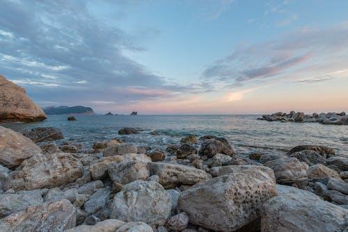 Vast water of rippling ocean with stony coast
