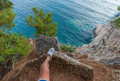 From above of anonymous male traveler standing on edge of rocky cliff above above azure rippling sea in tropical country