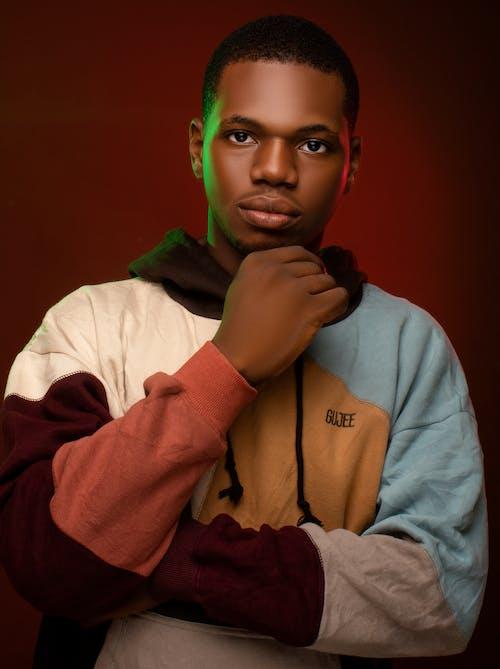 Serious young black man touching chin in studio