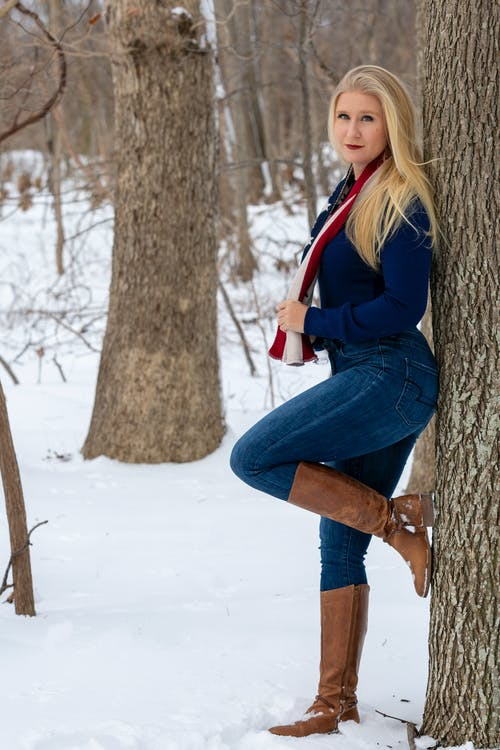 Woman in Black and Red Jacket and Blue Denim Jeans Sitting on Tree Trunk