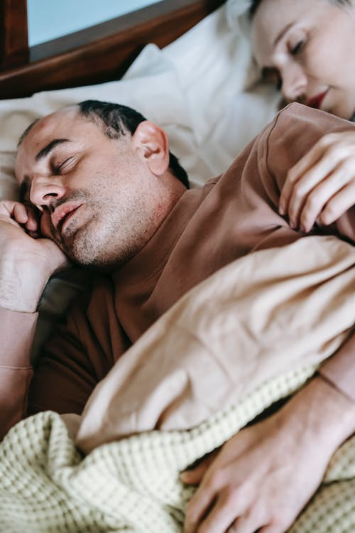 Calm couple sleeping in soft bed