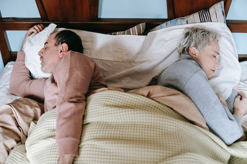 From above side view of middle aged diverse spouses in warm clothes sleeping lying back to back in comfortable bed in morning