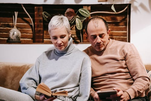 Concentrated middle aged diverse spouses in casual clothes sitting together on sofa while reading book and using tablet during weekend at home