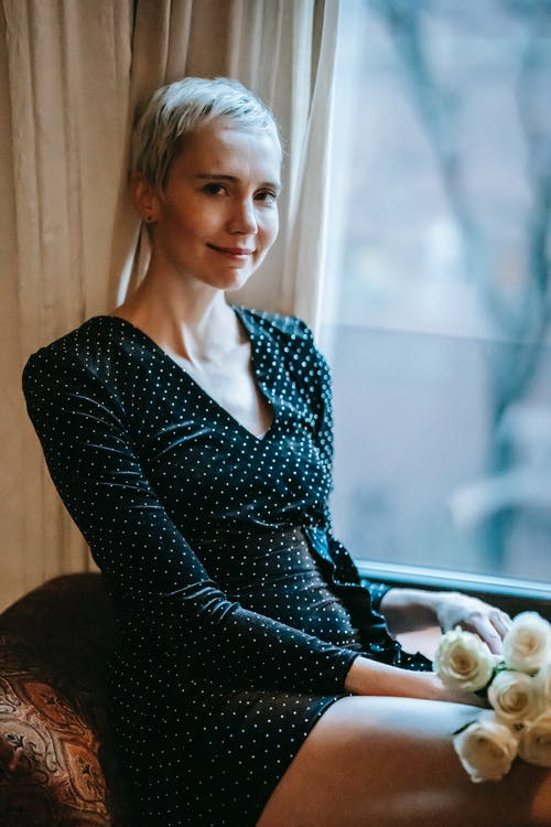 Content adult woman with short blond gain in stylish mini dress sitting on chair near window with bunch of elegant white roses and looking at camera
