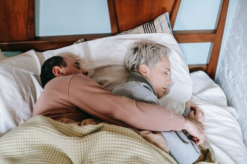 From above of middle aged ethnic man in casual clothes lying on bed and embracing wife while sleeping together on comfortable bed in sunny morning