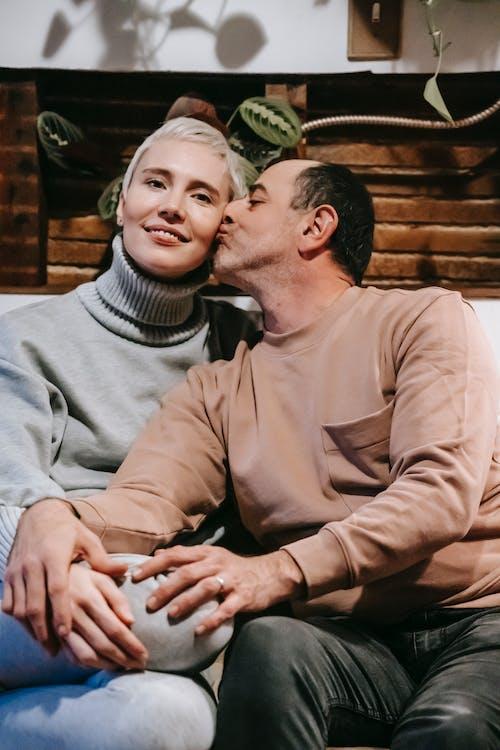 Enamored ethnic man kissing cheek of smiling wife