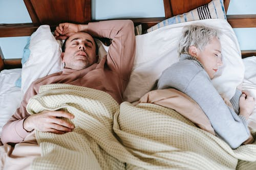 Diverse spouses sleeping on bed under plaid