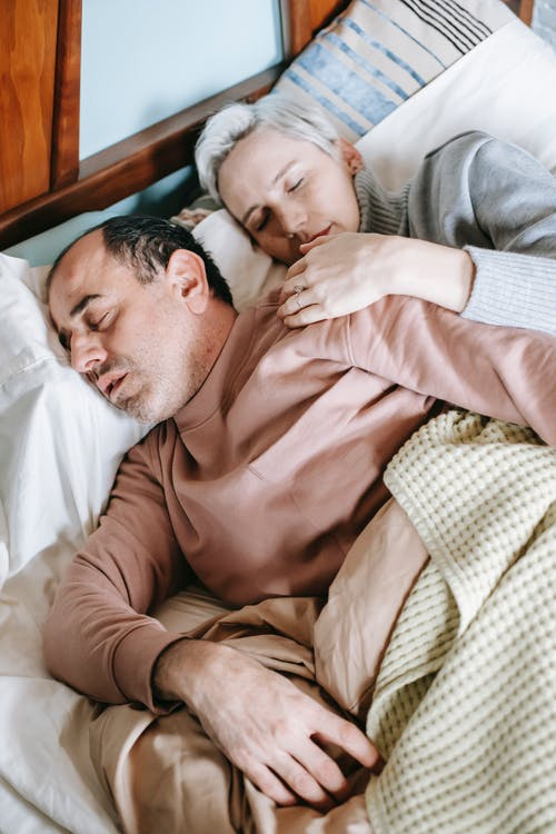 From above of adult woman in warm clothes embracing back of ethnic husband while sleeping together on comfortable bed in sunny morning