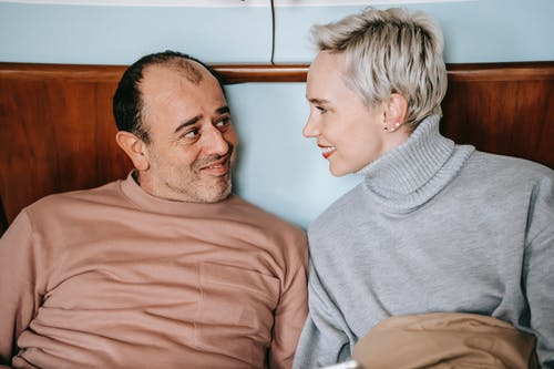 Happy adult woman and ethnic man in casual clothes smiling and looking at each other while sitting on bed during weekend at home
