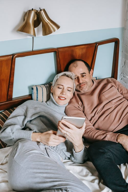 Delighted diverse couple lying on bed and sharing tablet