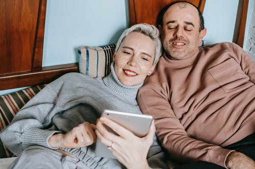 Content diverse middle aged married couple in warm casual clothes lying together on bed and smiling while watching movie on tablet