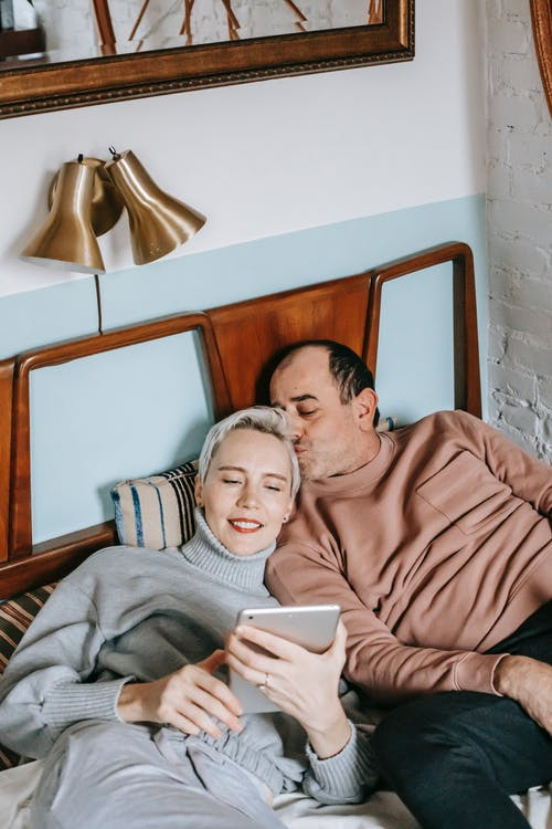 Happy ethnic man kissing head of wife using tablet on bed