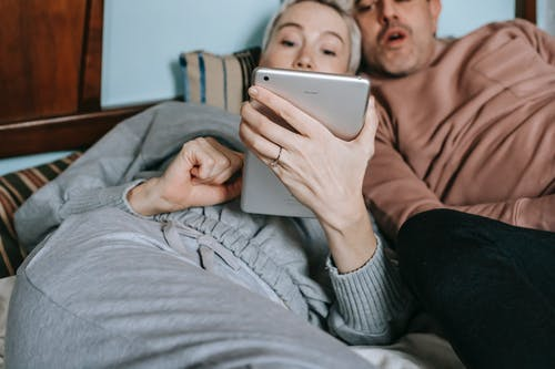 Crop adult diverse married couple in casual clothes cuddling while lying on bed and watching interesting movie on tablet